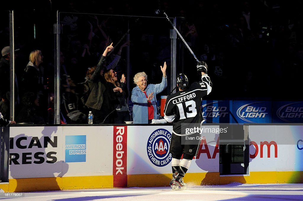 Kyle Clifford #13 of the Los Angeles Kings gives his stick to a fan following a victory against the Columbus Blue Jackets at Staples Center on February 15, 2013 in Los Angeles, California.