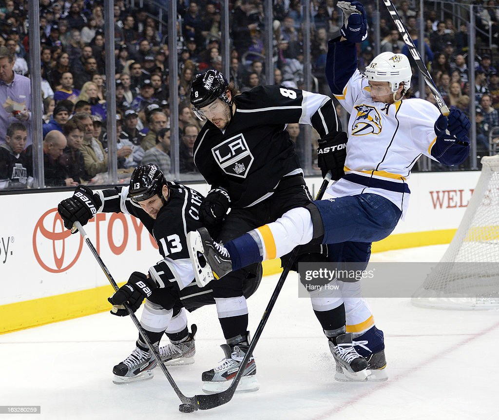 Kyle Clifford #13 of the Los Angeles Kings grabs control of the puck as Drew Doughty #8 of the Los Angeles Kings and Mike Fisher #12 of the Nashville Predators collide before the boards during the first period at Staples Center on March 4, 2013 in Los Angeles, California.