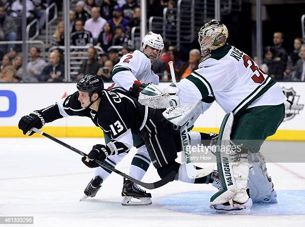 Kyle Clifford of the Los Angeles Kings is knocked to the ice by Darcy Kuemper and Keith Ballard of the Minnesota Wild during the second period at...