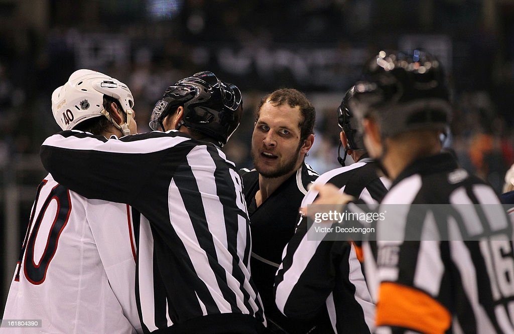 Kyle Clifford #13 of the Los Angeles Kings looks to referee Brian Pochmara #16 as linesmen break up the scrum between Clifford and Jared Boll #40 of the Columbus Blue Jackets after the play is whistled dead during the NHL game at Staples Center on February 15, 2013 in Los Angeles, California. The Kings defeated the Blue Jackets 2-1.