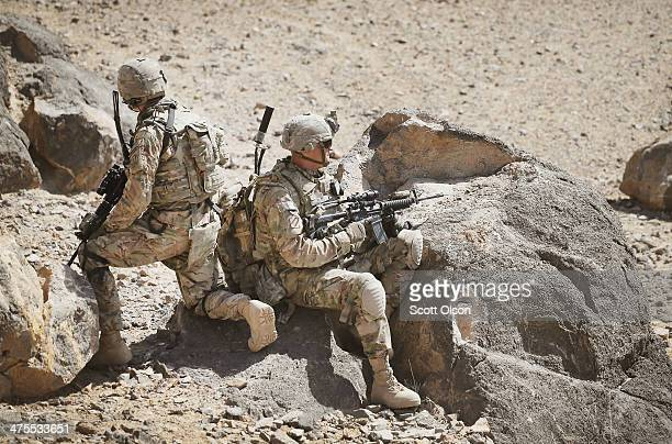 Kyle Cooper and SGT Anthony Blake from Columbia Missouri with the US Army's 4th squadron 2d Cavalry Regiment keep watch during a patrol of a hillside...