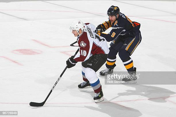 Kyle Cumiskey of the Colorado Avalanche handles the puck against Derek Roy of the Buffalo Sabres at HSBC Arena on January 9 2010 in Buffalo New York...