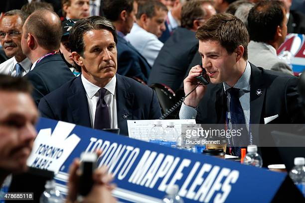Kyle Dubas Assistant General Manager of the Toronto Maple Leafs talks on the phone as President Brendan Shanahan looks on during the first round of...
