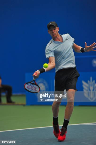 Kyle Edmund of Britain hits a return against Bernard Tomic of Australia during their men's singles first round match at the ATP Chengdu Open tennis...