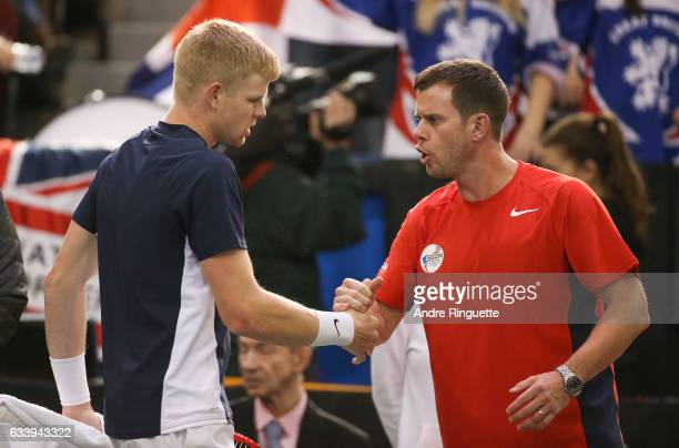 Kyle Edmund of Great Britain shakes hands with team captain Leon Smith during his singles match against Denis Shapovalov of Canada on day three of...