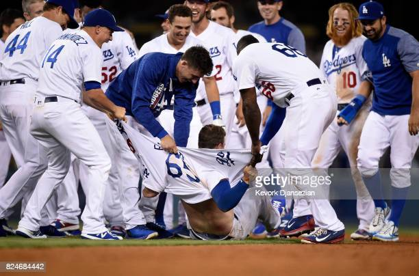 Kyle Farmer of the Los Angeles Dodgers has his shirt ripped apart by teammates Enrique Hernandez Cody Bellinger and Yasiel Puig after hitting the...