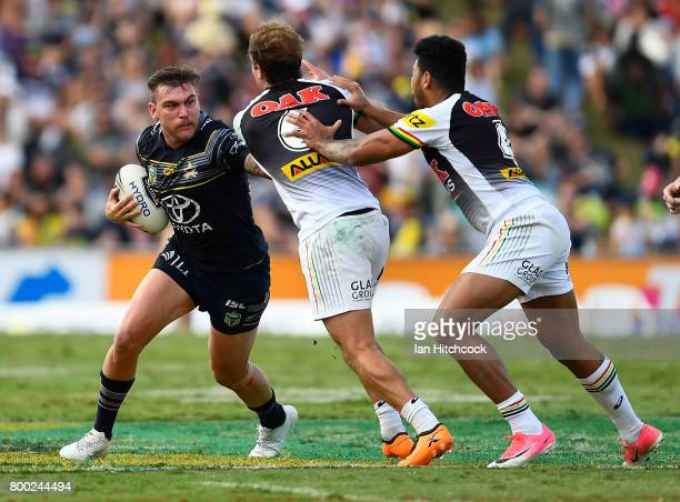 Kyle Feldt of the Cowboys is tackled by Matthew Moylan of the Panthers and Waqa Blake of the Panthers during the round 16 NRL match between the North...