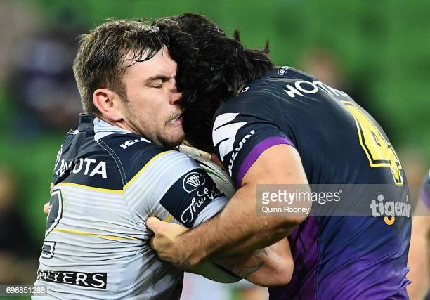 Kyle Feldt of the Cowboys is tackled by Tohu Harris of the Storm during the round 15 NRL match between the Melbourne Storm and the North Queensland...