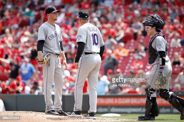Kyle Freeland of the Colorado Rockies talks to manager Bud Black and catcher Ryan Hanigan before he is taken out in the sixth inning of a game...