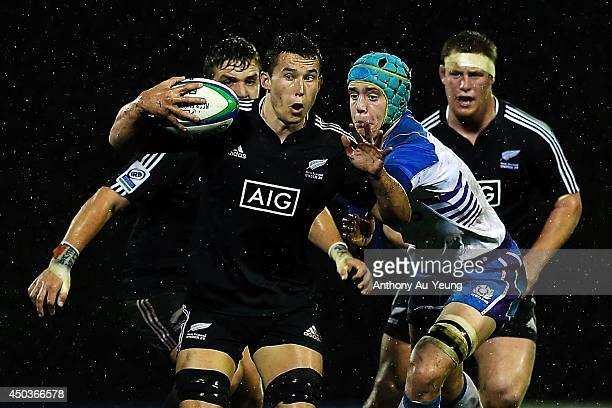 Kyle Harris of New Zealand on the charge against Lewis Carmichael of Scotland during the 2014 Junior World Championship match between New Zealand and...