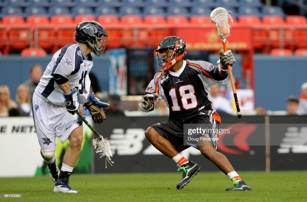 Kyle Harrison of the Denver Outlaws controls the ball as Benson Erwin of the Washington Bayhawks defends during Major League Lacrosse action at...