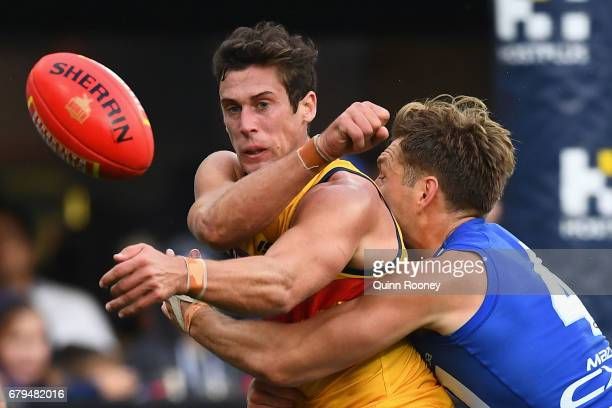 Kyle Hartigan of the Crows handballs whilst being tackled by Shaun Higgins of the Kangaroos during the round seven AFL match between the North...
