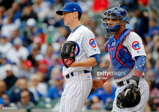 Kyle Hendricks of the Chicago Cubs and Willson Contreras talk on the pitcher's mound between pitches against the Washington Nationals during the...