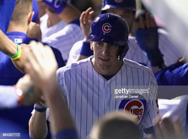 Kyle Hendricks of the Chicago Cubs is congratulated in the dugout after laying down a run scoring bunt in the 3rd inning against the Cincinnati Reds...