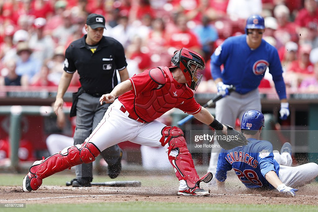 Kyle Hendricks #28 of the Chicago Cubs scores a run ahead of the tag attempt by Tucker Barnhart #16 of the Cincinnati Reds after a sacrifice fly by Arismendy Alcantara in the third inning of the game at Great American Ball Park on July 10, 2014 in Cincinnati, Ohio.
