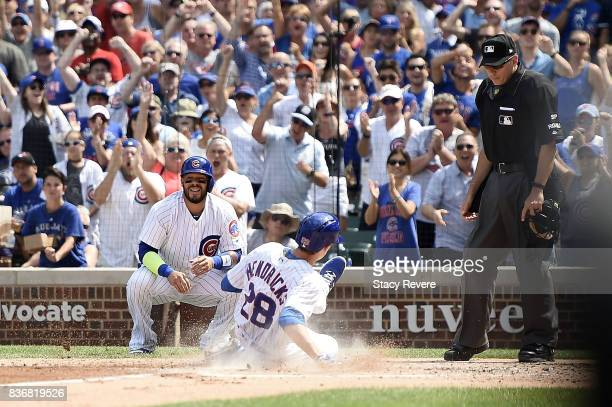 Kyle Hendricks of the Chicago Cubs slides safely into home plate during a game against the Toronto Blue Jays at Wrigley Field on August 20 2017 in...