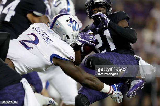 Kyle Hicks of the TCU Horned Frogs carries the ball against Dorance Armstrong Jr #2 of the Kansas Jayhawks in the first quarter at Amon G Carter...