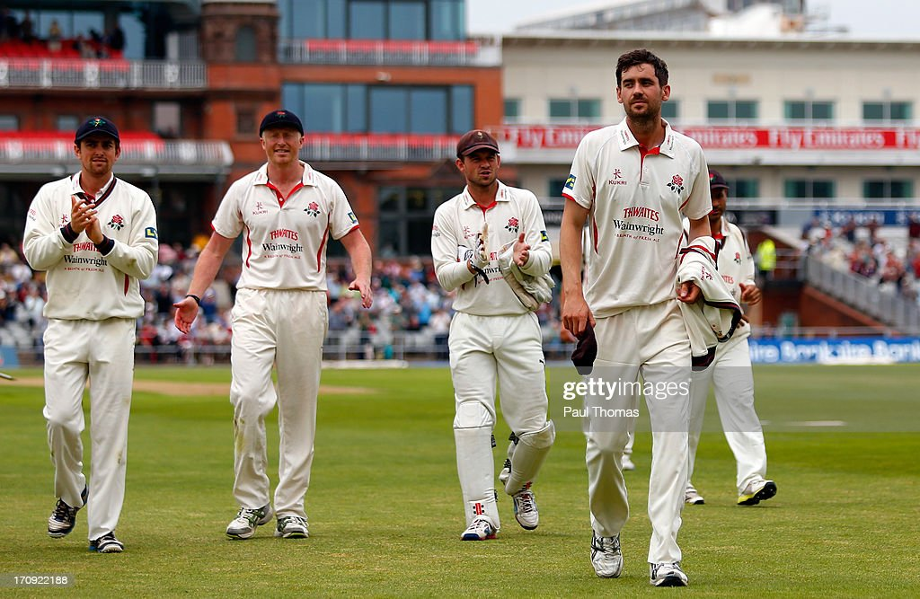 Kyle Hogg (R) of Lancashire is applauded from the field by team mates after taking 7 wickets during day one of the LV County Championship Division Two match between Lancashire and Northamptonshire at Old Trafford on June 20, 2013 in Manchester, England.