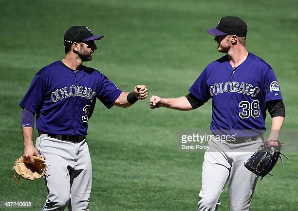 Kyle Kendrick of the Colorado Rockies right congratulates Daniel Descalso of the Colorado Rockies after an inning ending double play during the fifth...