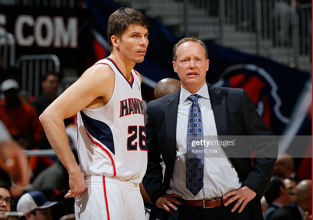 Kyle Korver and Mike Budenholzer of the Atlanta Hawks converse during the game against the Cleveland Cavaliers at Philips Arena on December 6 2013 in...