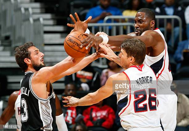 Kyle Korver defends as Elton Brand of the Atlanta Hawks blocks a pass by Marco Belinelli of the San Antonio Spurs at Philips Arena on October 17 2013...