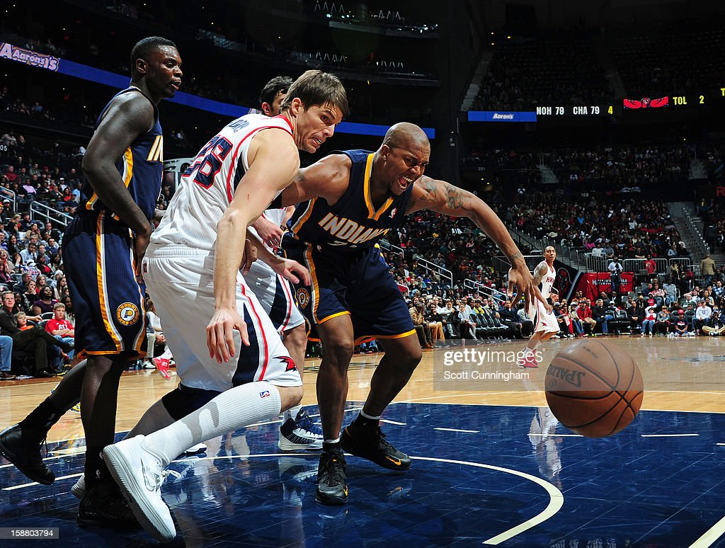 Kyle Korver #26 of the Atlanta Hawks battles for a loose ball against David West #21 of the Indiana Pacers on December 29, 2012 at Philips Arena in Atlanta, Georgia.