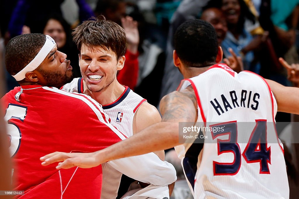 Kyle Korver #26 of the Atlanta Hawks celebrates with Josh Smith #5 and Devin Harris #34 after hitting a go-ahead three-point basket against the Washington Wizards in the final seconds at Philips Arena on November 21, 2012 in Atlanta, Georgia.