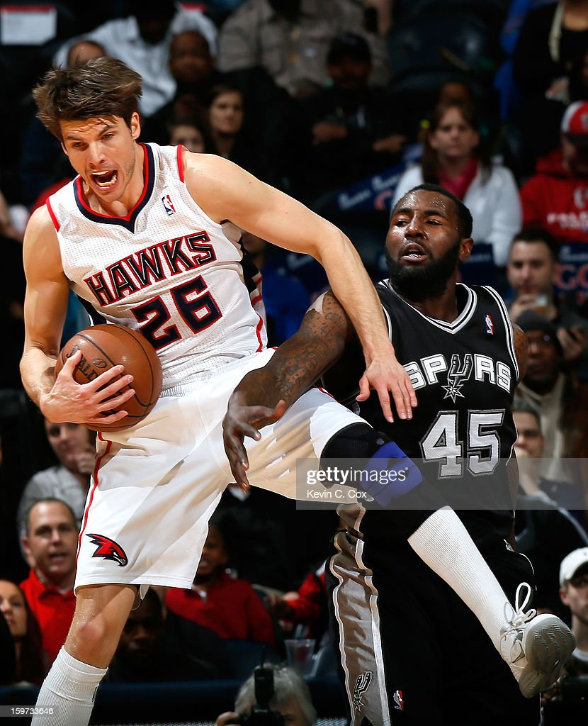 Kyle Korver #26 of the Atlanta Hawks grabs a rebound against DeJuan Blair #45 of the San Antonio Spurs at Philips Arena on January 19, 2013 in Atlanta, Georgia.