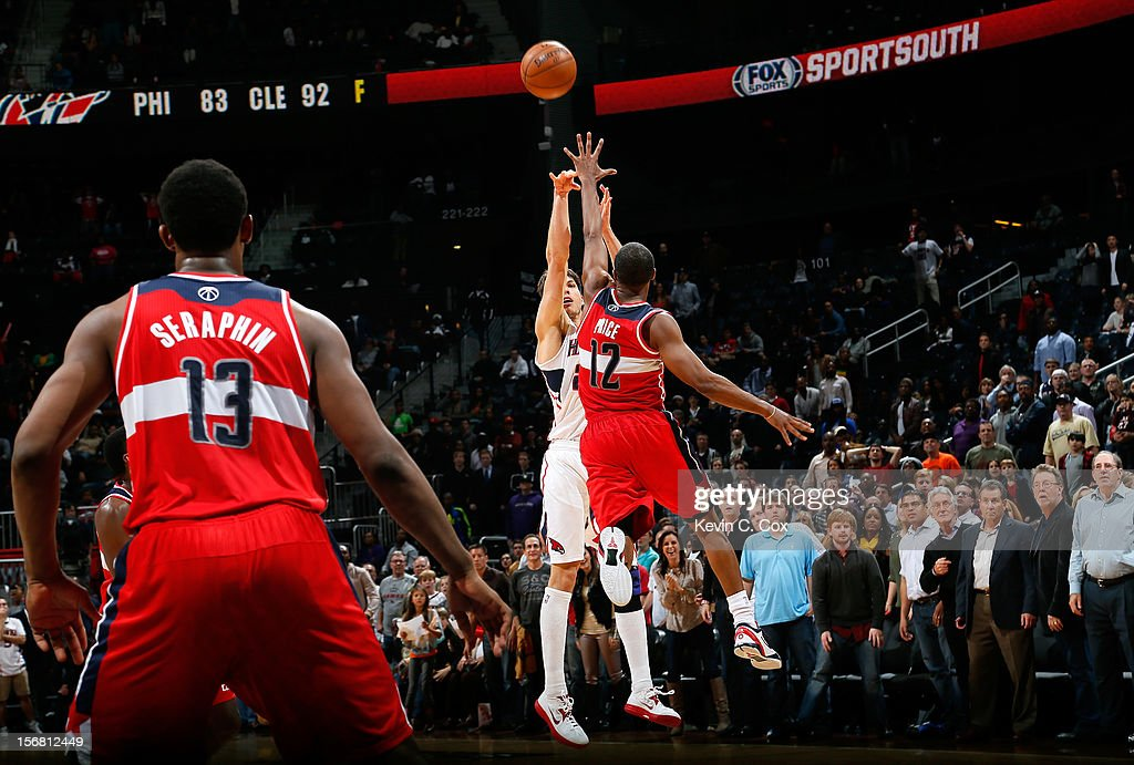 Kyle Korver #26 of the Atlanta Hawks hits a go-ahead three-point basket over A.J. Price #12 of the Washington Wizards in the final seconds at Philips Arena on November 21, 2012 in Atlanta, Georgia.