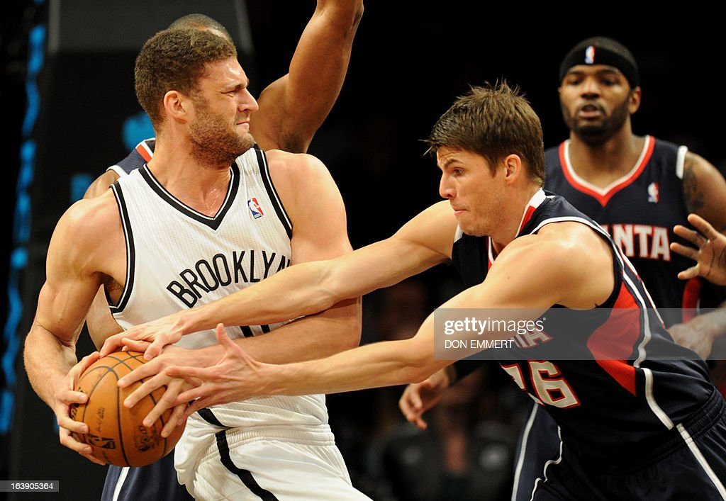 Kyle Korver (R) of the Atlanta Hawks tries to steal the ball from Brooklyn Nets Brook Lopez March 17, 2013 at the Barclay Center in New York.