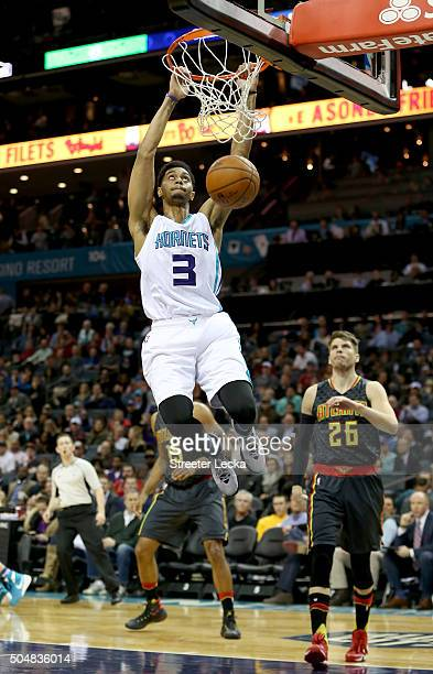 Kyle Korver of the Atlanta Hawks watches as Jeremy Lamb of the Charlotte Hornets dunks the ball during their game at Time Warner Cable Arena on...