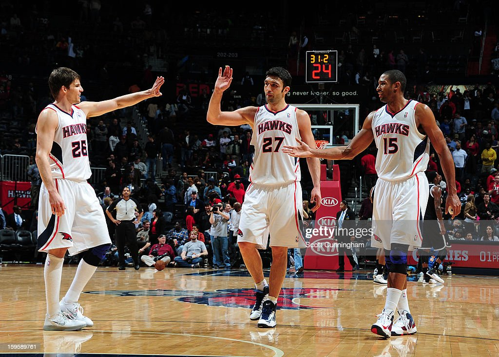Kyle Korver #26, Zaza Pachulia #27, and Al Horford #15 of the Atlanta Hawks celebrate during the game against the Brooklyn Nets on January 16, 2013 at Philips Arena in Atlanta, Georgia.