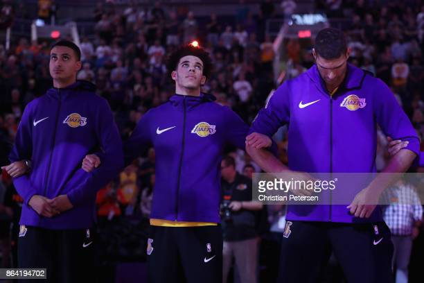 Kyle Kuzma Lonzo Ball and Brook Lopez of the Los Angeles Lakers stand arm in arm for the national anthem before the NBA game against the Phoenix Suns...