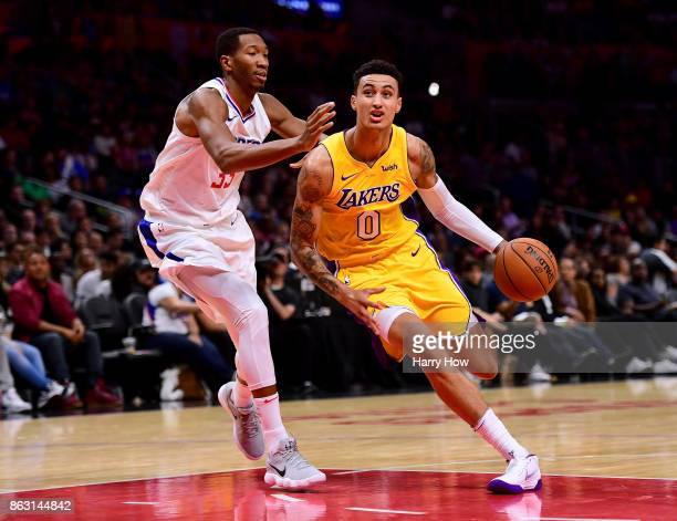 Kyle Kuzma of the Los Angeles Lakers drives on Wesley Johnson of the LA Clippers at Staples Center on October 10 2017 in Los Angeles California