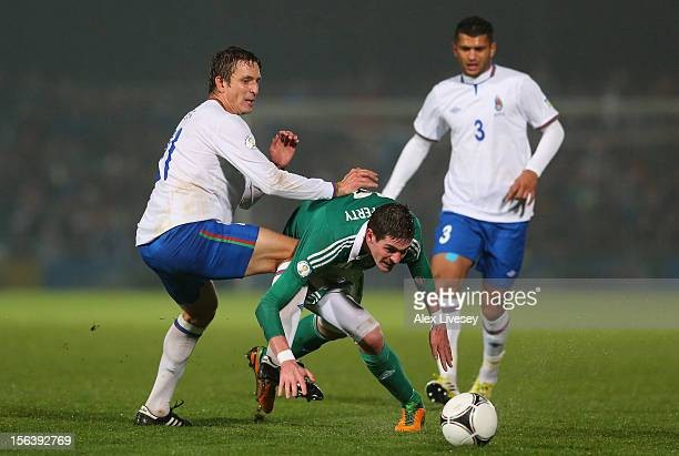 Kyle Lafferty of Northern Ireland beats Volodimir Levin of Azerbaijan during the FIFA 2014 World Cup Group F Qualifying match between Northern...
