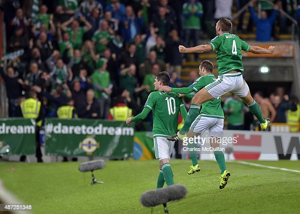 Kyle Lafferty of Northern Ireland celebrates with team mates Gareth McAuley and Niall McGinn after scoring during the Euro 2016 Group F qualifying...