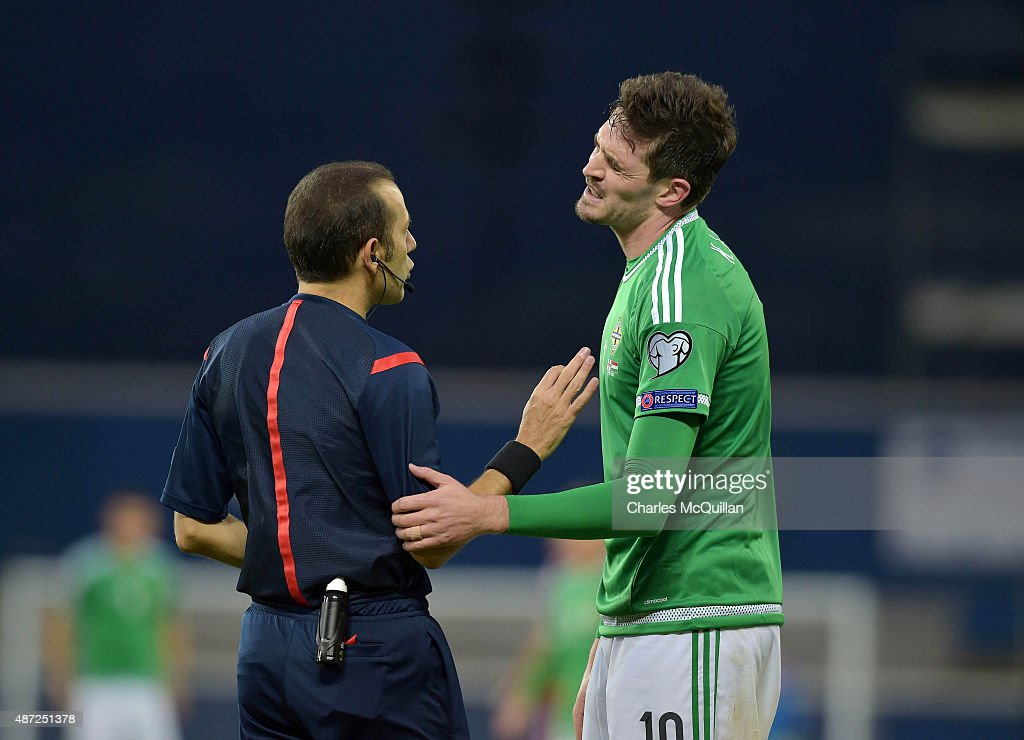 Kyle Lafferty (R) of Northern Ireland receives a yellow card from referee Cuneyt Cakir during the Euro 2016 Group F qualifying match between Northern Ireland and Hungary at Windsor Park on September 7, 2015 in Belfast, Northern Ireland.