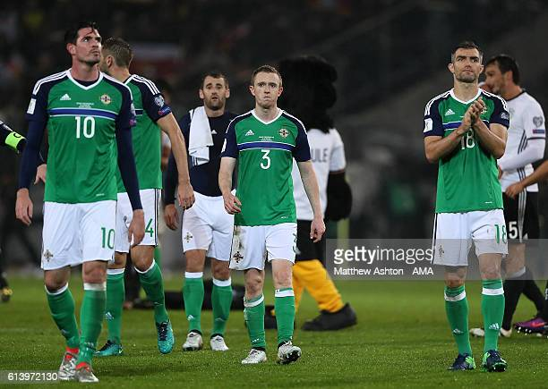 Kyle Lafferty Shane Ferguson and Aaron Hughes of Northern Ireland walk off at the end of the FIFA 2018 World Cup Qualifier between Germany and...
