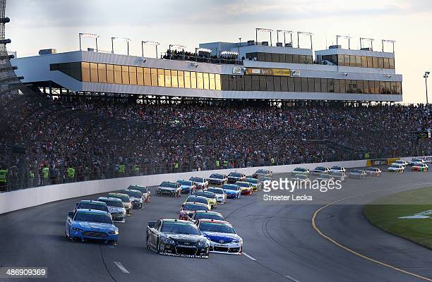 Kyle Larson driver of the AXE Peace Chevrolet leads the field on the first lap of the NASCAR Sprint Cup Series Toyota Owners 400 at Richmond...