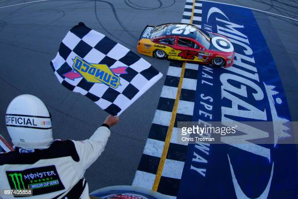 Kyle Larson driver of the Cars 3/Target Chevrolet takes the checkered flag to win the Monster Energy NASCAR Cup Series FireKeepers Casino 400 at...