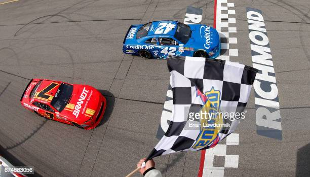 Kyle Larson driver of the Credit One Bank Chevrolet takes the checkered flag as Justin Allgaier driver of the BRANDT Chevrolet places second during...