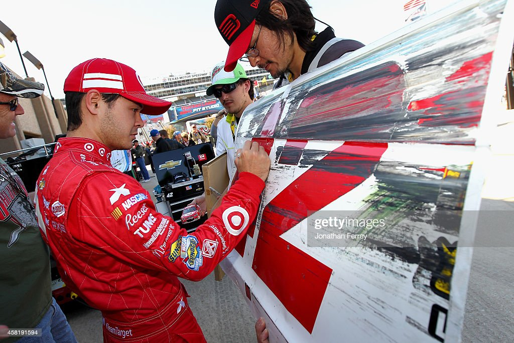 Kyle Larson driver of the Philips Norelco Chevrolet signs an autograph during practice for the NASCAR Nationwide Series O'Reilly Auto Parts Challenge...