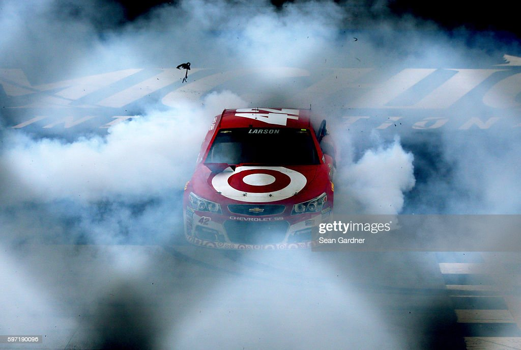 Kyle Larson driver of the Target Chevrolet celebrates with a burnout after winning the NASCAR Sprint Cup Series Pure Michigan 400 at Michigan...