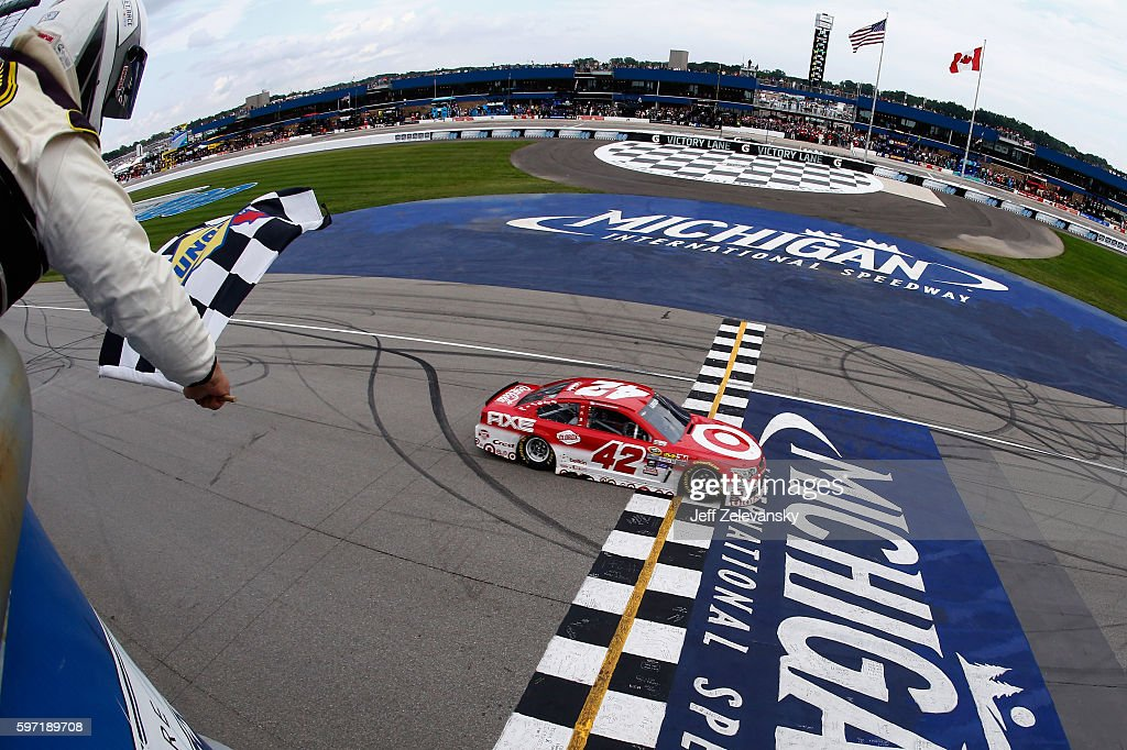 Kyle Larson, driver of the #42 Target Chevrolet, takes the checkered flag to win the NASCAR Sprint Cup Series Pure Michigan 400 at Michigan International Speedway on August 28, 2016 in Brooklyn, Michigan.