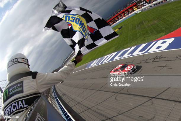 Kyle Larson driver of the Target Chevrolet takes the checkered flag to win the Monster Energy NASCAR Cup Series Auto Club 400 at Auto Club Speedway...