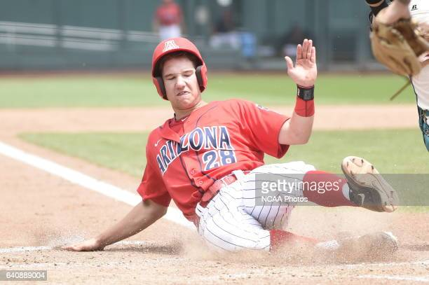 Kyle Lewis of the University of Arizona receives scores a run with a safe slide against Coastal Carolina University during Game 3 of the Division I...