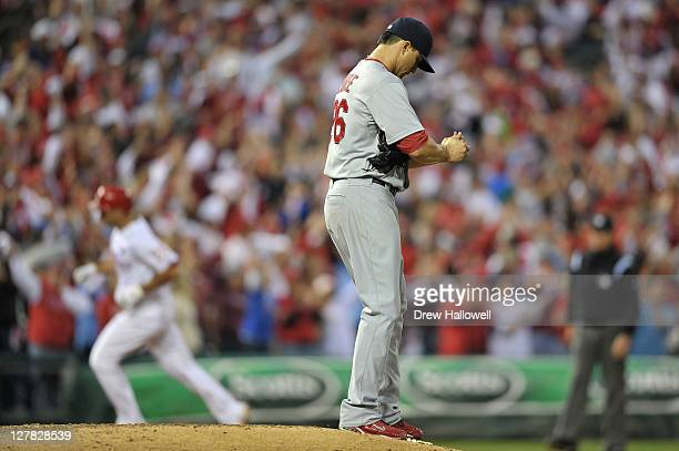 Kyle Lohse of the St Louis Cardinals stands on the mound as Raul Ibanez of the Philadelphia Phillies rounds the bases after hitting a tworun home run...