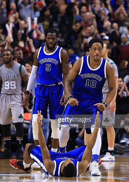 Kyle Lowry of the Toronto Raptors celebrates a 3pointer as DeMar DeRozan helps him up during the second half of an NBA game against the Boston...