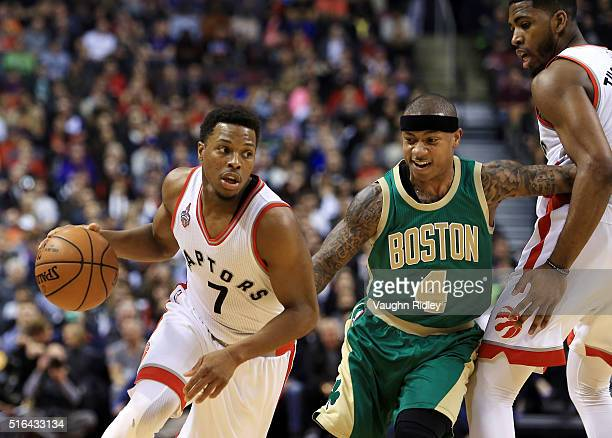 Kyle Lowry of the Toronto Raptors dribbles the ball as Isaiah Thomas of the Boston Celtics is blocked by Jason Thompson during the second half of an...
