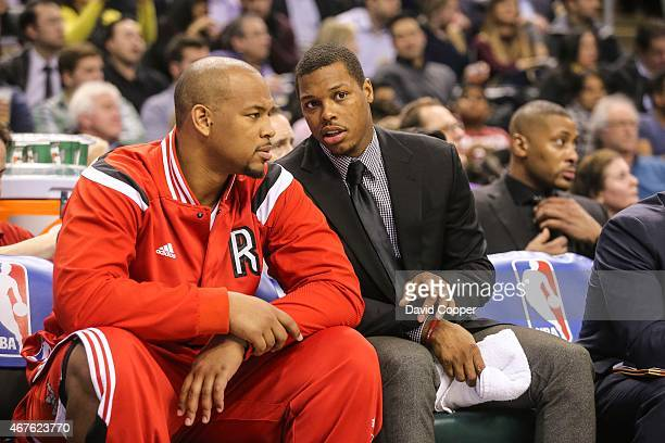 Kyle Lowry of the Toronto Raptors in a suit talks with Chuck Hayes of the Toronto Raptors on the bench during the game between the Toronto Raptors...